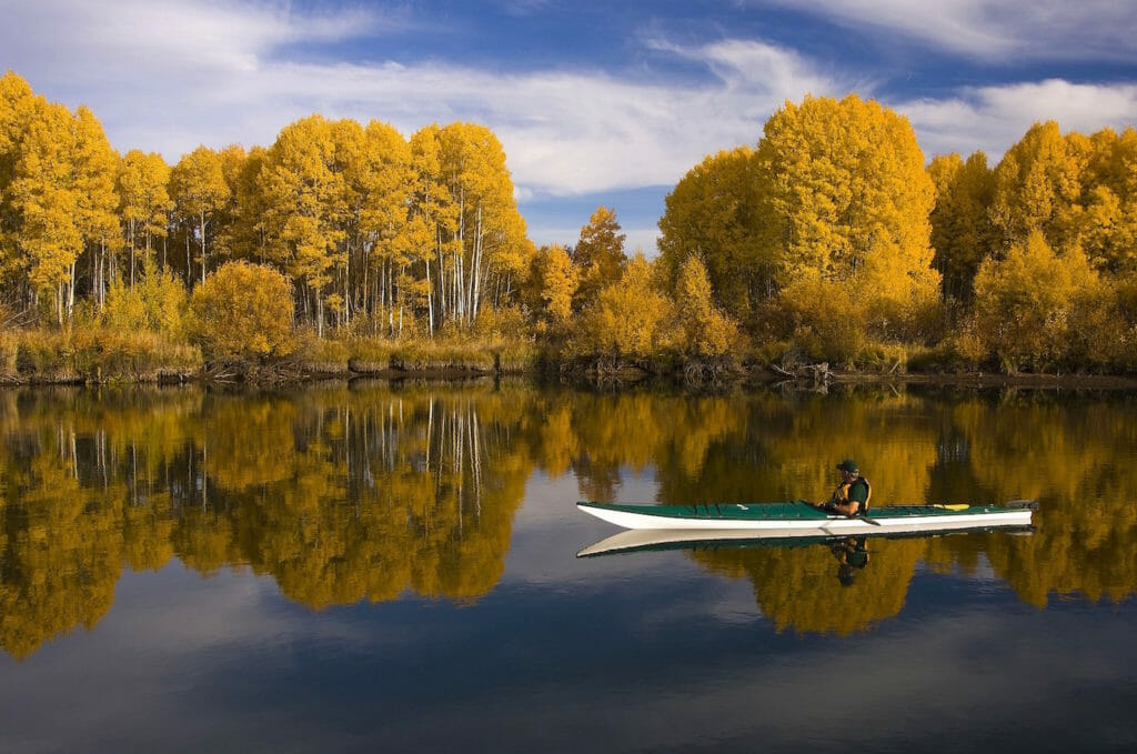 Kayaker on a small lake with fall colors
