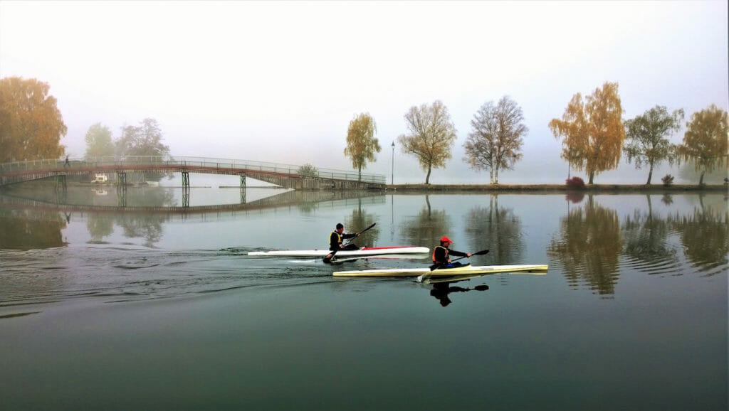 Kayakers paddling in foggy conditions with fall colors