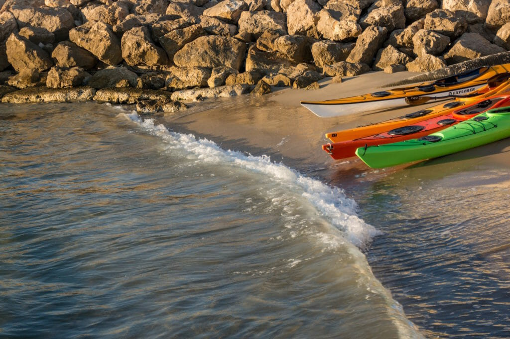 Kayaks on a rocky and sandy beach with a wave